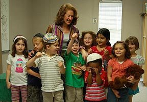Sheila Aron with children holding threads.