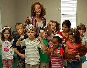 Sheila Aron, author of I'm Glad I'm Me, with children holding threads.